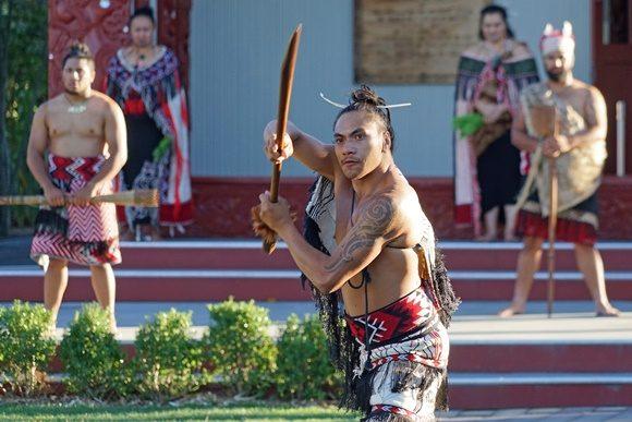 Maori com braço tatuado empunhando arma de madeira em dança típica