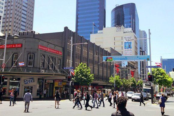 Pessoas andando numa rua cheia de lojas com prédios ao fundo
