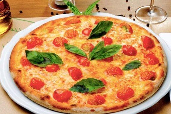 Pizza com tomates cereja e grandes folhas de manjericão