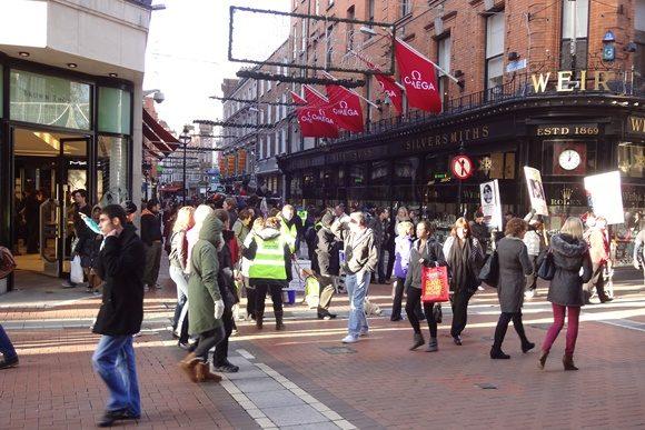 Rua cheia de pessoas passando e fachadas de lojas