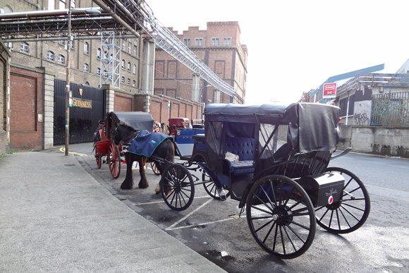 Fachada da fábrica da Guiness com nome escrito no portão e carruagem a diante