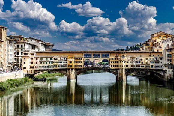 Ponte vista à distância com céu azul acima e rio abaixo