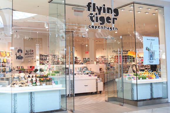 Fachada da loja com vitrines e porta de vidro e nome no alto
