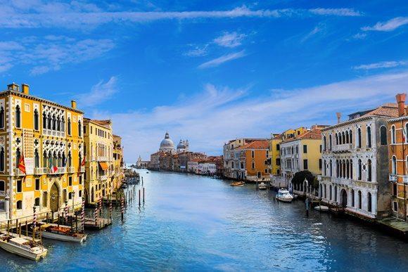 Canal passando no meio de construções em Veneza, com cúpula da igreja aparecendo ao fundo