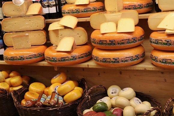 Loja de queijos com queijos grandes cortados e outros menores inteiros em cestas
