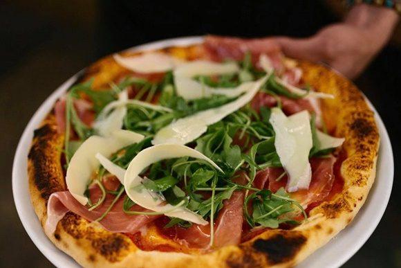 Mão segurando prato com pizza com presunto cru, rúcula e grandes lascas de parmesão