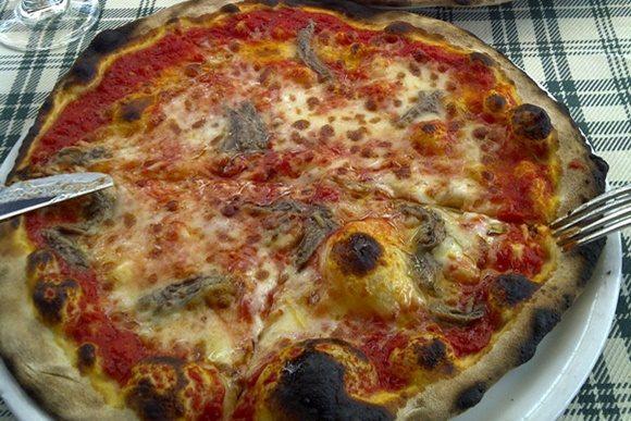 Pizza com anchovas, molho e muçarela no prato com garfo e faca nas bordas