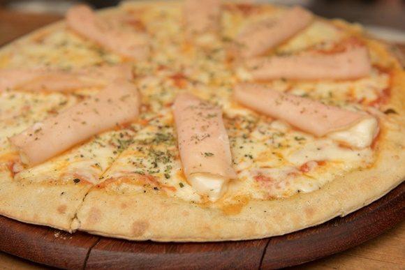 Pizza com peito de peru sobre a massa