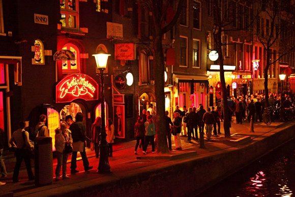 Ruas com iluminação vermelha e pessoas passando