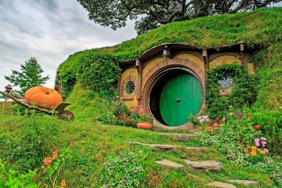 Casa com porta redonda e coberta por grama com abóbora gigante de enfeite ao lado