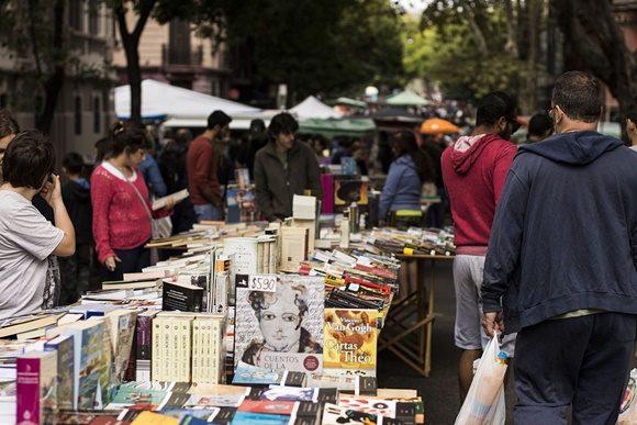 Feira da Tristan Navaja com barraquinhas cheias de livros e pessoas passando ao lado