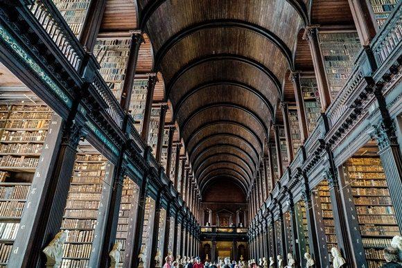 Biblioteca da faculdade com teto alto de madeira e estantes enormes com vários livros