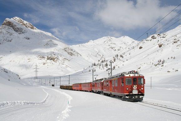 Trem passando no meio de uma montanha nevada