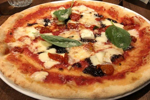 Pizza com queijo de cabra, cebola caramelizada e grandes folhas de manjericão