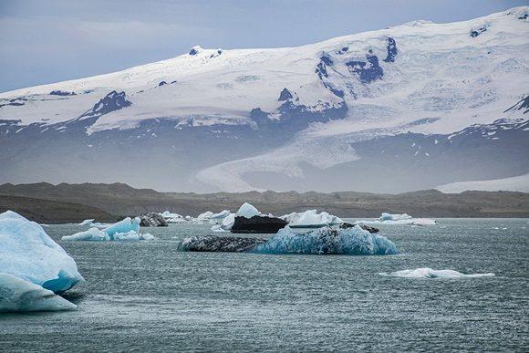 Lago com icebergs no meio e montanha congelada ao fundo