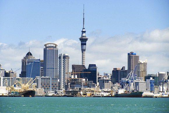 Vista de Auckland com torre ao fundo, ao lado de outros prédios e mar à frente
