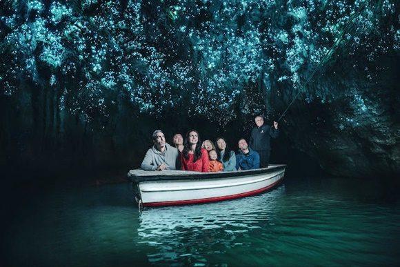 Barquinho passando dentro de caverna com pessoas olhando o céu iluminado