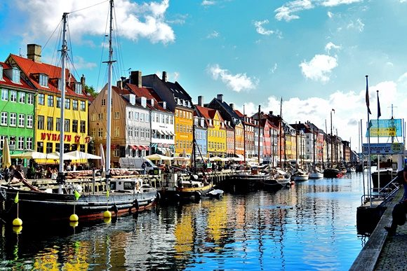 Casinhas diante do rio de com barcos em frente em Nyhavn