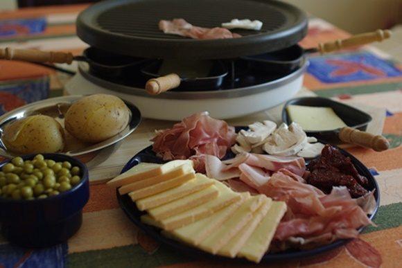 Panela de raclette ao fundo com potes com batata, ervilhas, queijo e presuntos diante dela