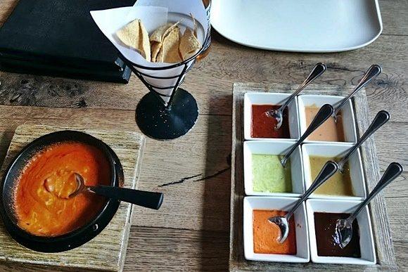 Pequena frigideira com a mistura de feijão e queijos, cone com nachos e bandeja com seis tipos de molhos