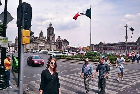 Érika no fim de uma faixa de pedestres numa rua em frente ao Zócalo com uma bandeira do México ao fundo