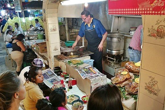 Box de comida, com cozinheiro e panelas atrás e clientes, esperando, na frente