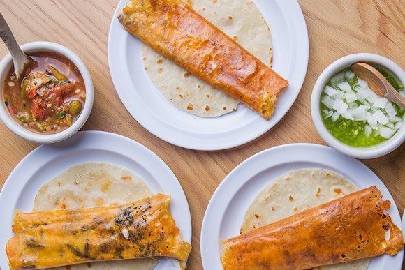 Três pratos com tipos diferentes de tacos com potinhos com molhos ao lado