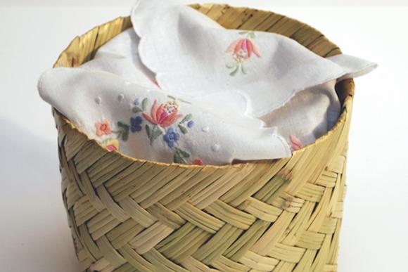Cestinha de palha com pano de prato bordado, dobrado dentro