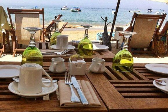 Mesa arrumada com talheres, xícaras, taças e guardanapos de tecido