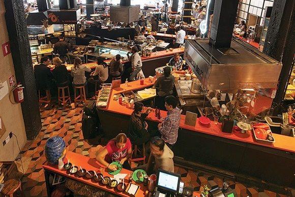 Parte interna do mercado vista de cima com vários estandes com clientes sentados em banquinhos