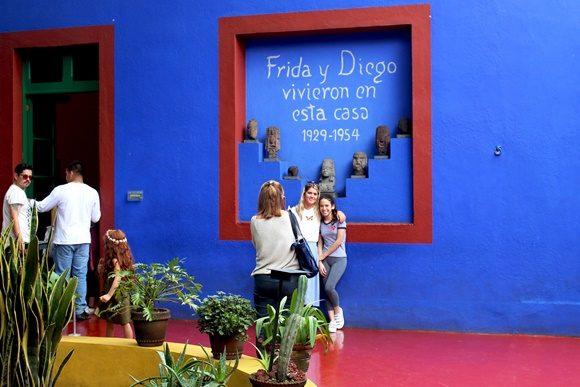 Parede azul do museu com uma moldura grande tipo de janela, onde está escrito que Frida e Diego viveram lá de 1929 a 1954 e pessoas posando em frente