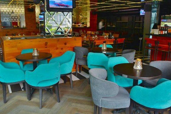 Salão do restaurante com mesas menores com poltronas largas verdes